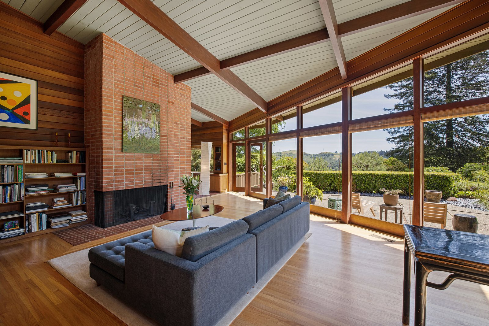 A closer look at the living area and original brick fireplace. Floor-to-ceiling windows enclose the room on two sides, with French doors opening to the patio.  Photo 4 of 21 in An Impeccable Midcentury Compound in the Berkeley Hills Wants $3.4M