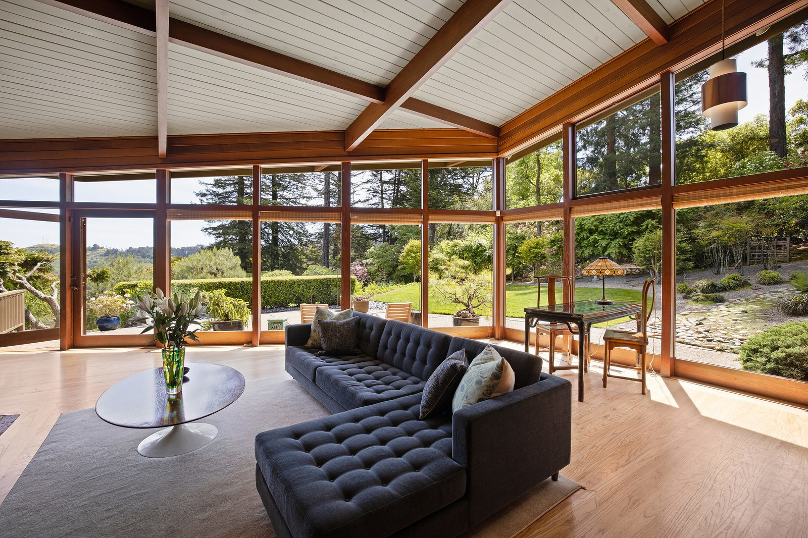 A look at the wall of glass that continues around a corner of the living room.  Photo 5 of 21 in An Impeccable Midcentury Compound in the Berkeley Hills Wants $3.4M