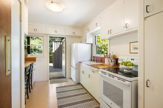 The kitchen features a full-sized range and refrigerator, as well as wraparound cabinetry.