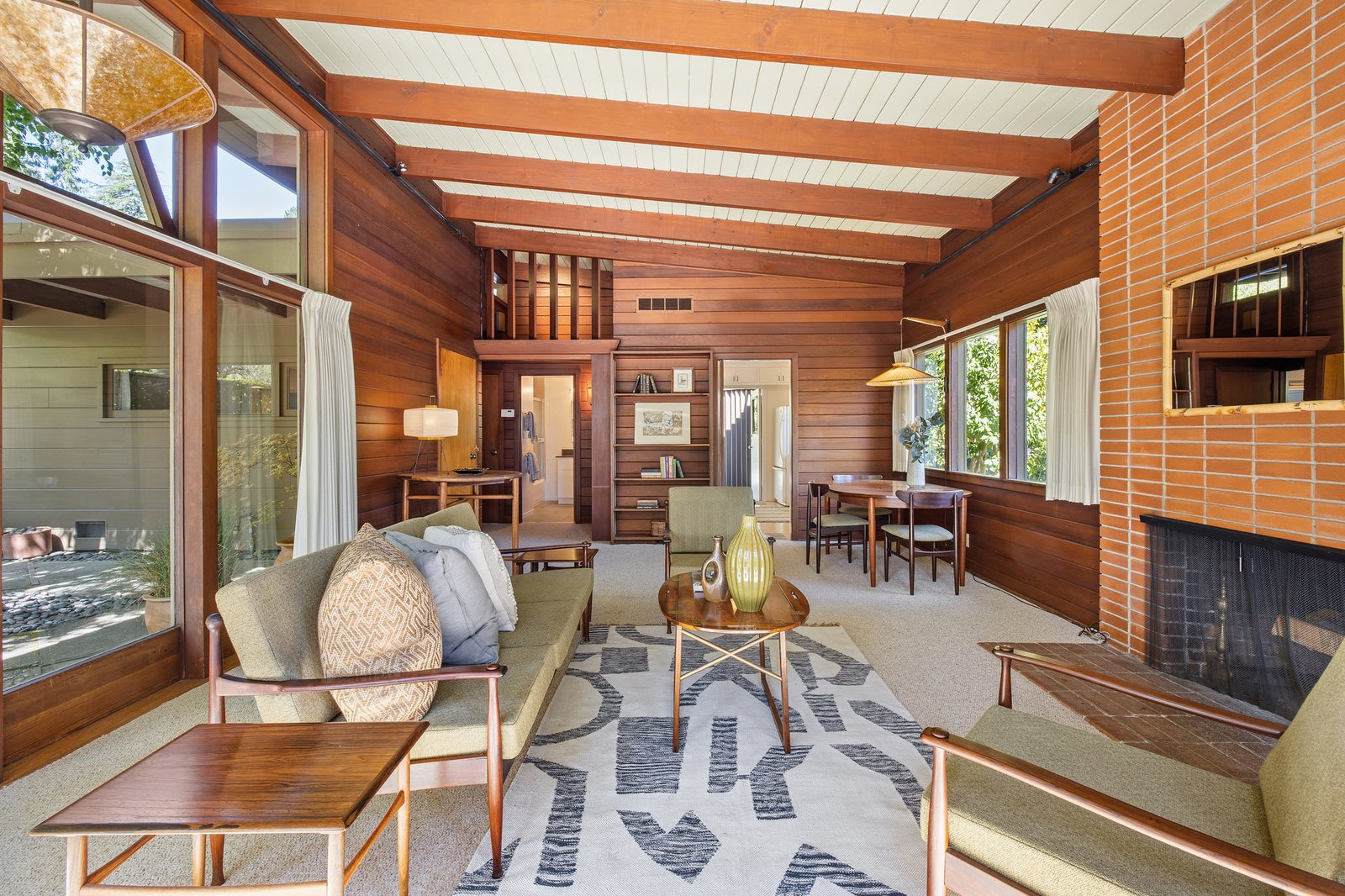 At the back of the living room is a dining area adjacent to the kitchen. The bedroom and bathroom area are accessible from a small hallway to the left.  Photo 18 of 21 in An Impeccable Midcentury Compound in the Berkeley Hills Wants $3.4M