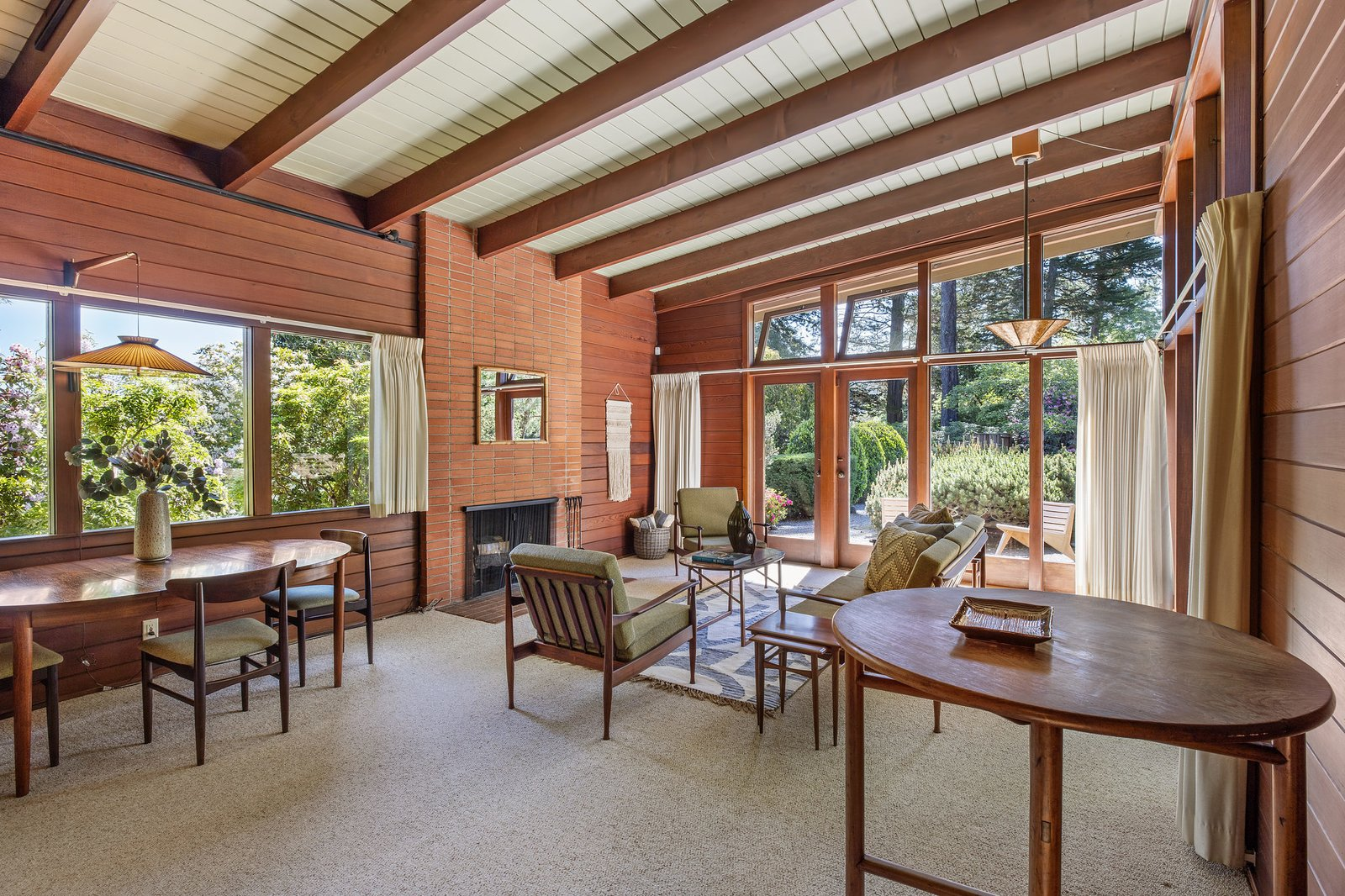 Though smaller in size, the guesthouse features a similar palette of materials. Wood-clad walls complement an original brick fireplace and a wall of windows.  Photo 17 of 21 in An Impeccable Midcentury Compound in the Berkeley Hills Wants $3.4M