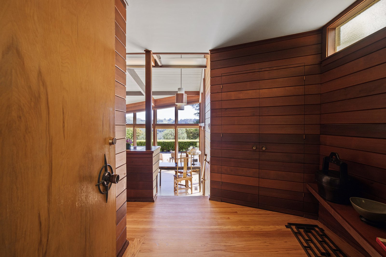 Dark wood clads the walls of the entranceway, which leads to a bright, spacious living room.  Photo 2 of 21 in An Impeccable Midcentury Compound in the Berkeley Hills Wants $3.4M