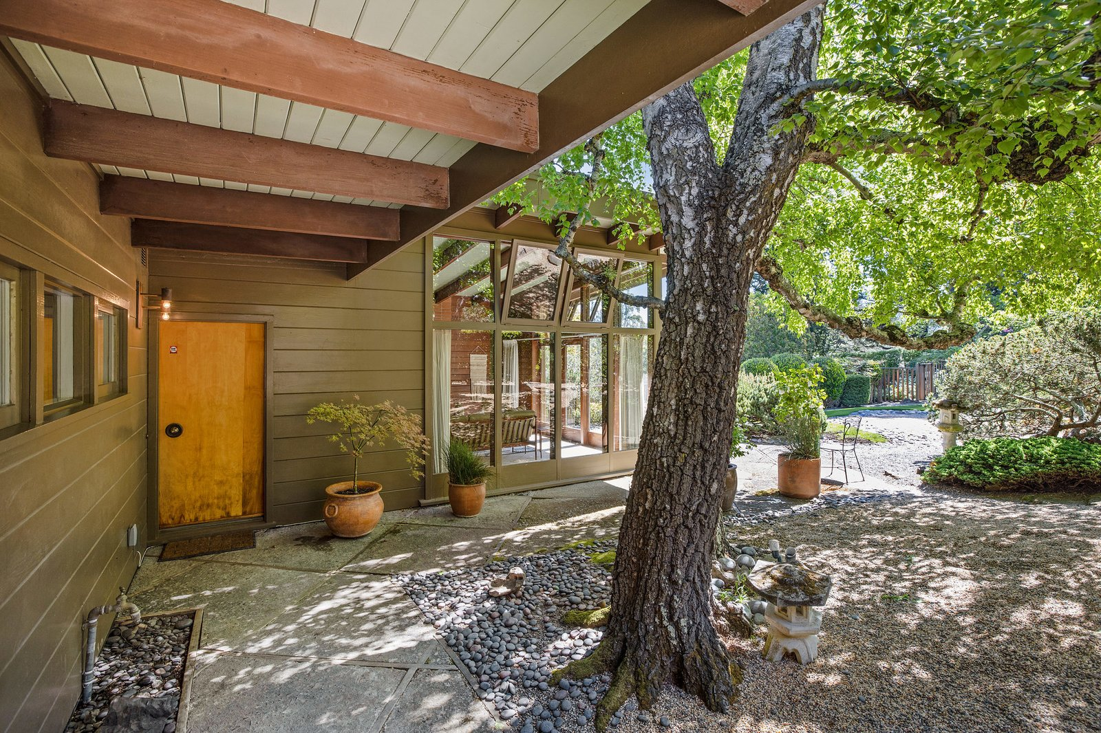 The detached structure offers an additional bedroom and bathroom, as well as a full kitchen and glass-encased living area.  Photo 16 of 21 in An Impeccable Midcentury Compound in the Berkeley Hills Wants $3.4M