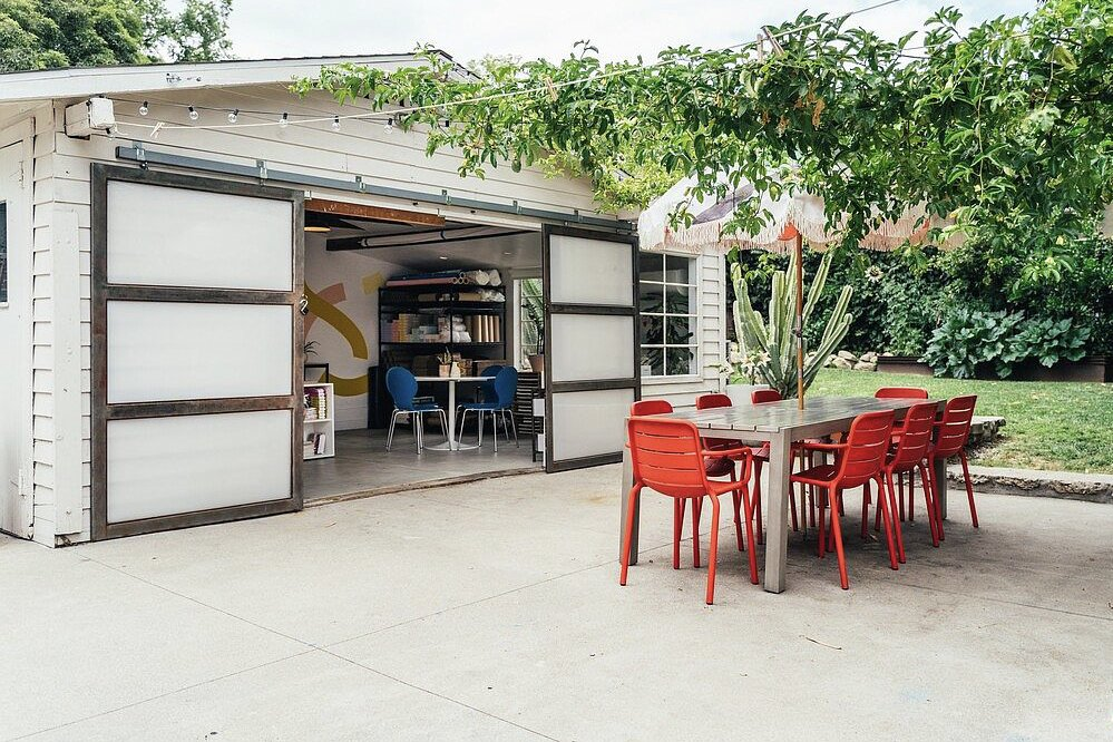 Outdoor, Back Yard, Trees, Hardscapes, Shrubs, and Grass In the backyard, a detached building is currently used as a workspace but could be converted back into a garage. A large cement patio provides space for entertaining.  Photo 14 of 16 in A Cheery Craftsman Duplex in L.A. With Adjacent Studio Space Asks $1.25M