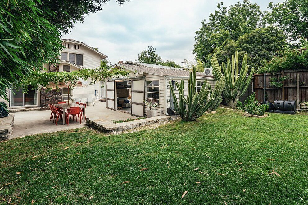Outdoor, Grass, Trees, and Shrubs A wooden fence lines the green lawn beyond the garage in the backyard.  Photo 16 of 16 in A Cheery Craftsman Duplex in L.A. With Adjacent Studio Space Asks $1.25M