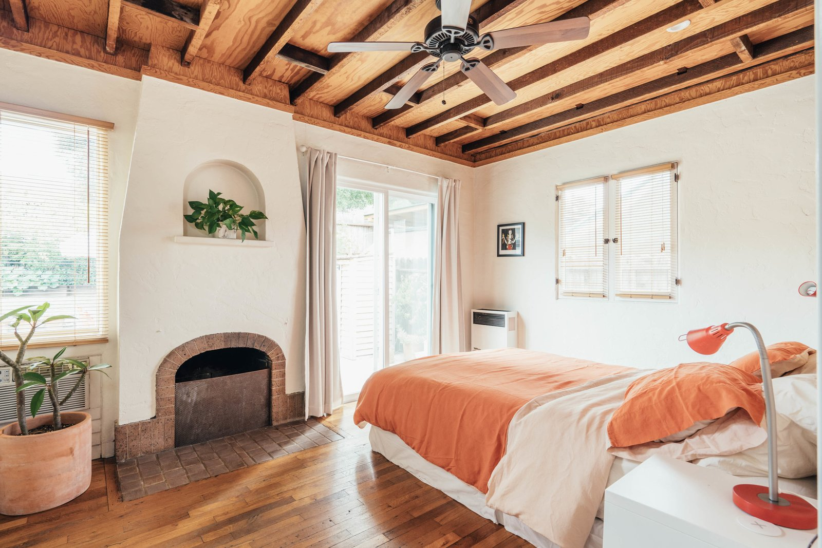 Bedroom, Bed, Night Stands, Table Lighting, and Dark Hardwood Floor Adjacent to the living area is the bedroom, which features another original fireplace.  Photo 11 of 16 in A Cheery Craftsman Duplex in L.A. With Adjacent Studio Space Asks $1.25M
