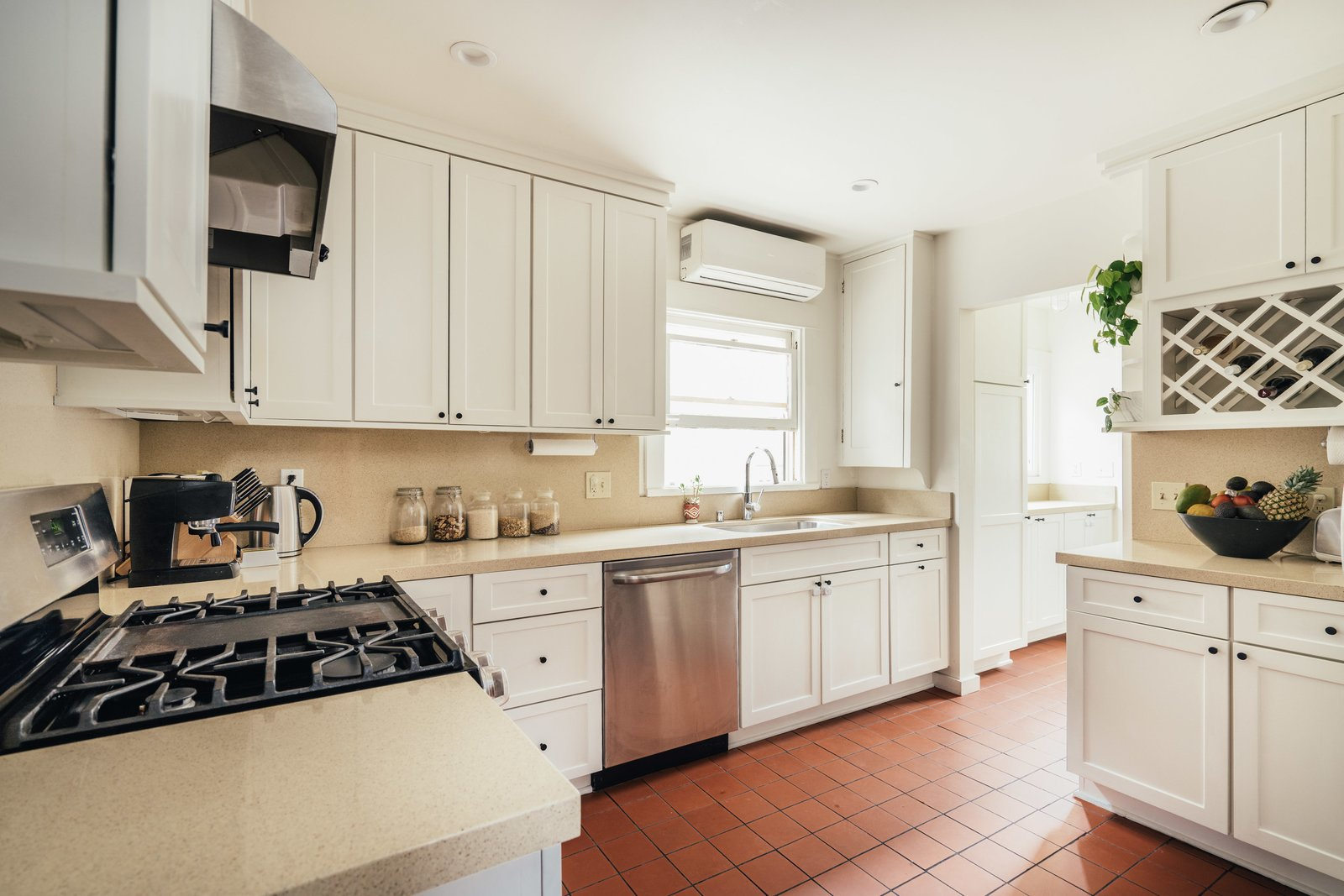 Kitchen, Range, White Cabinet, Range Hood, Drop In Sink, Brick Floor, Dishwasher, and Ceiling Lighting The fully renovated kitchen features custom cabinetry and new stainless-steel appliances.   Photo 6 of 16 in A Cheery Craftsman Duplex in L.A. With Adjacent Studio Space Asks $1.25M