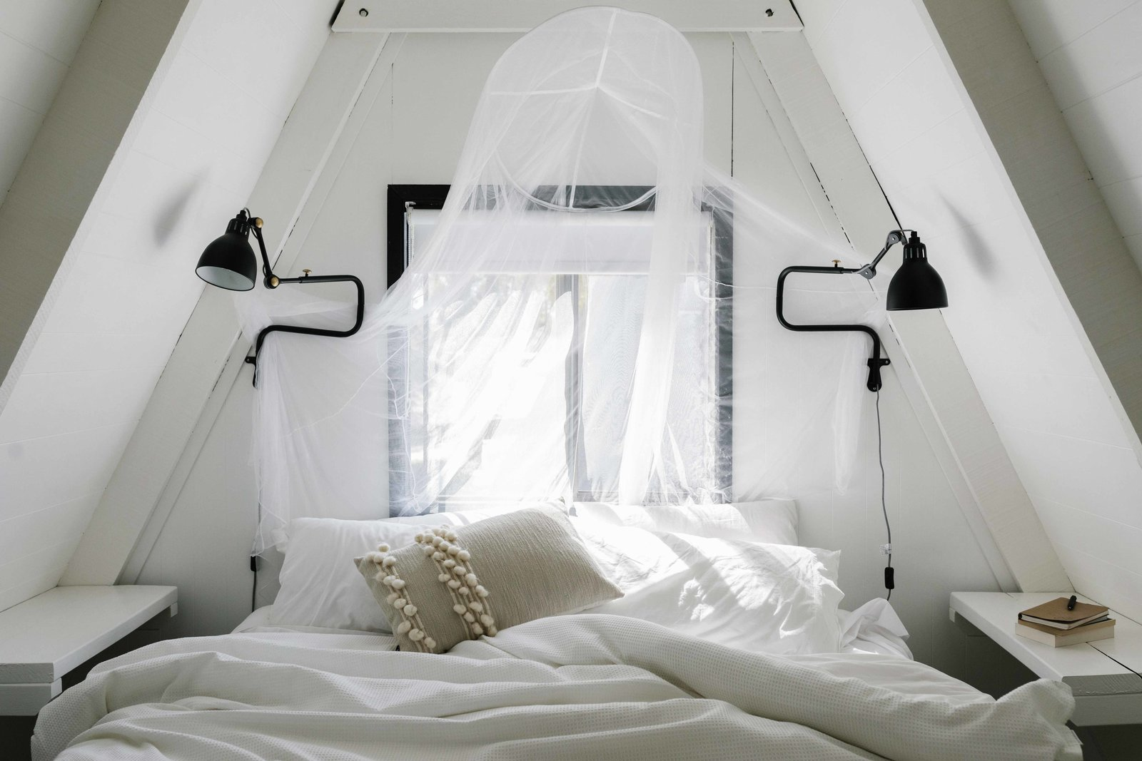Bedroom, Bed, Wall Lighting, Night Stands, Accent Lighting, and Lamps Inside, several of the larger A-frame cabins feature a bright second floor, which the couple updated with a simple coat of white paint. Their goal was to freshen the spaces without making them feel overly modern or fancy.  Photo 3 of 13 in A Cluster of A-Frames Hugs White Sand Dunes on Australia's Southwestern Coast