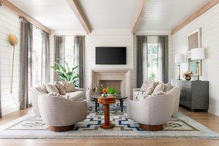 A blue-and-gold, geometric-patterned rug from Amadi grounds this living room designed by Cortney Bishop.