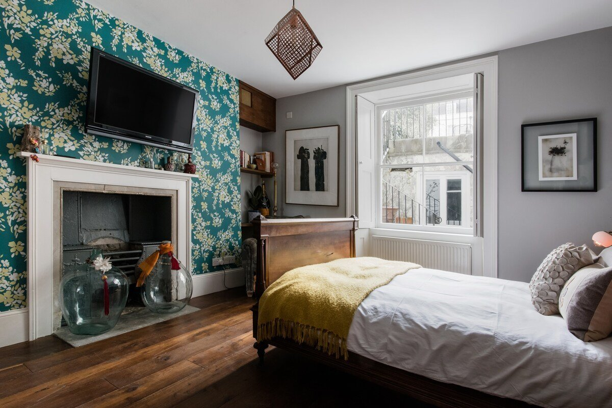 Bedroom, Bed, Shelves, Pendant Lighting, Ceiling Lighting, and Dark Hardwood Floor A look at one of the two bedrooms. The flat also offers one full bathroom.  Photo 3 of 13 in 6 Famous Writer's Retreats You Can Rent When You're Ready to Write That Novel
