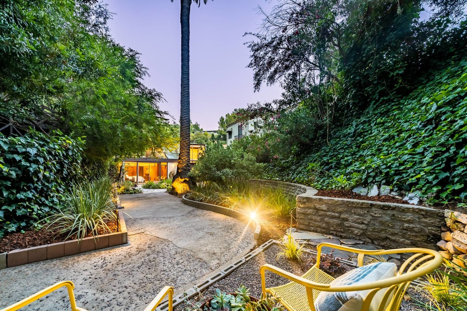 A path leads around to a smaller seating area at the bottom of the hillside.  Photo 15 of 15 in A John Lautner Post-and-Beam Hits the Market for the First Time Ever