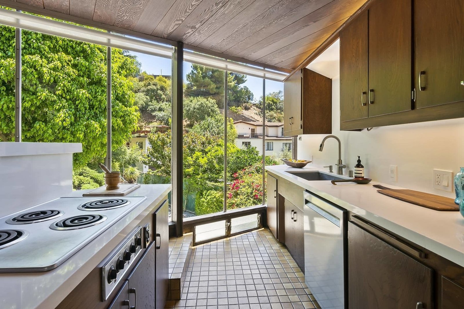 The kitchen features the original cabinetry, tile floors, and Frigidare cooktop and oven. All other appliances, along with the countertops and fixtures have been modernized.  Photo 8 of 15 in A John Lautner Post-and-Beam Hits the Market for the First Time Ever