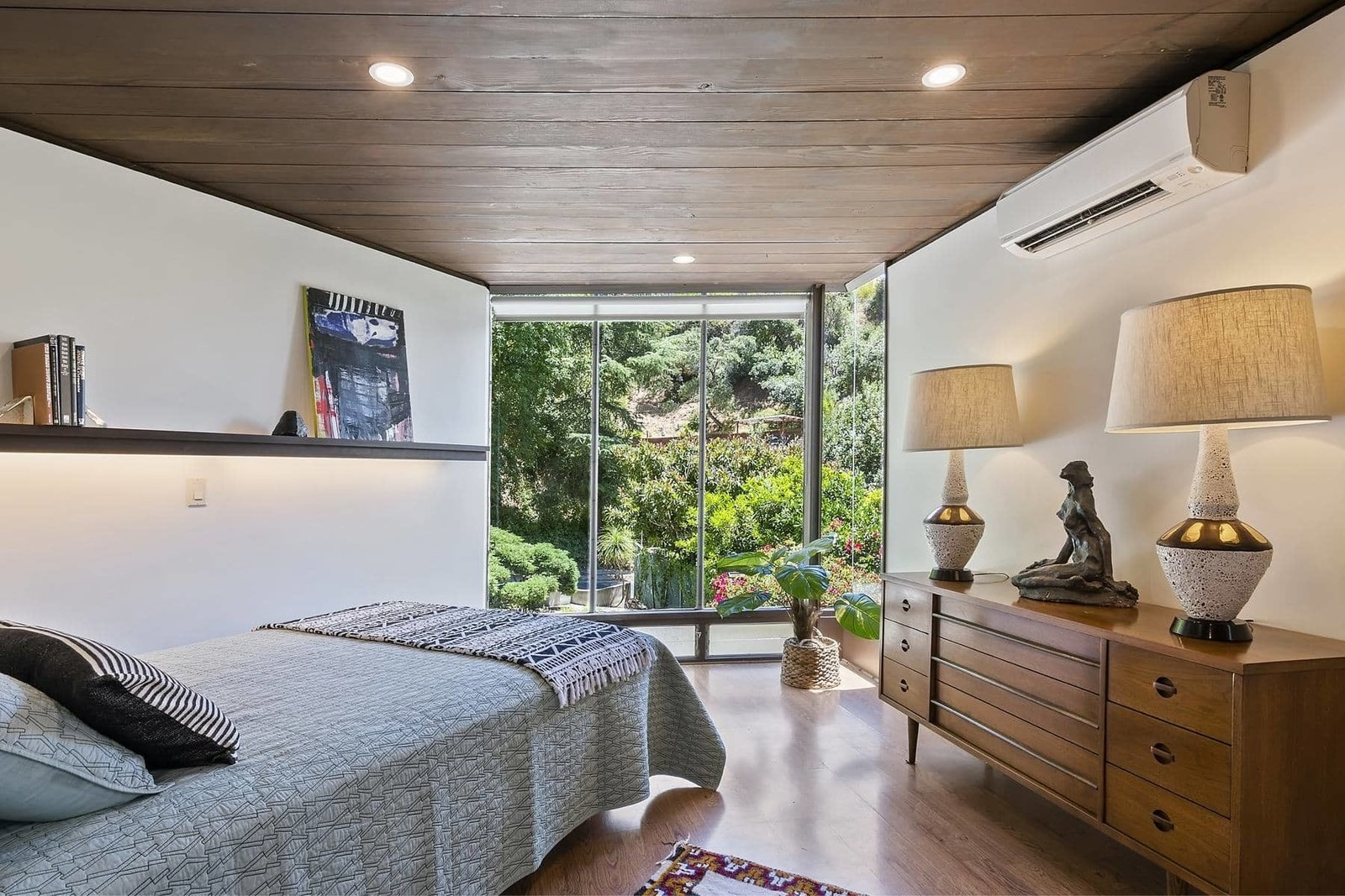 A look at one of two bedrooms on the upper level. The triangular-shaped space features a large wall of glass at one end and original wood-clad ceilings.  Photo 9 of 15 in A John Lautner Post-and-Beam Hits the Market for the First Time Ever