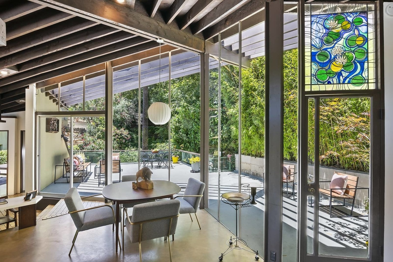 The dining area is surrounded on two sides by floor-to-ceiling glass. Several doors lead out to a large deck.  Photo 5 of 15 in A John Lautner Post-and-Beam Hits the Market for the First Time Ever
