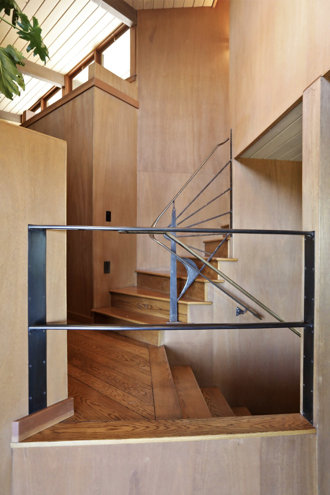 Steel railings define a staircase leading up to the second floor loft and bedrooms.  Photo 10 of 19 in An Alluring Berkeley Hills Home by a Case Study Architect Asks $2.9M