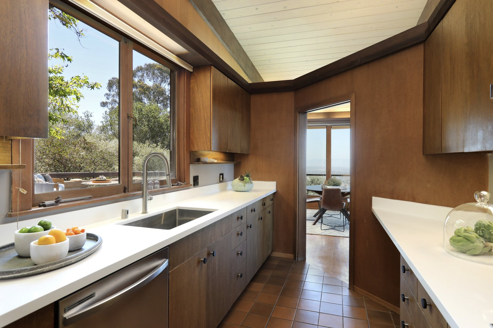 Just off the dining area, a galley-style kitchen offers new appliances, fixtures, and countertops. Other features, such as the cabinetry and flooring, are original to the 1994 reconstruction.  Photo 7 of 19 in An Alluring Berkeley Hills Home by a Case Study Architect Asks $2.9M