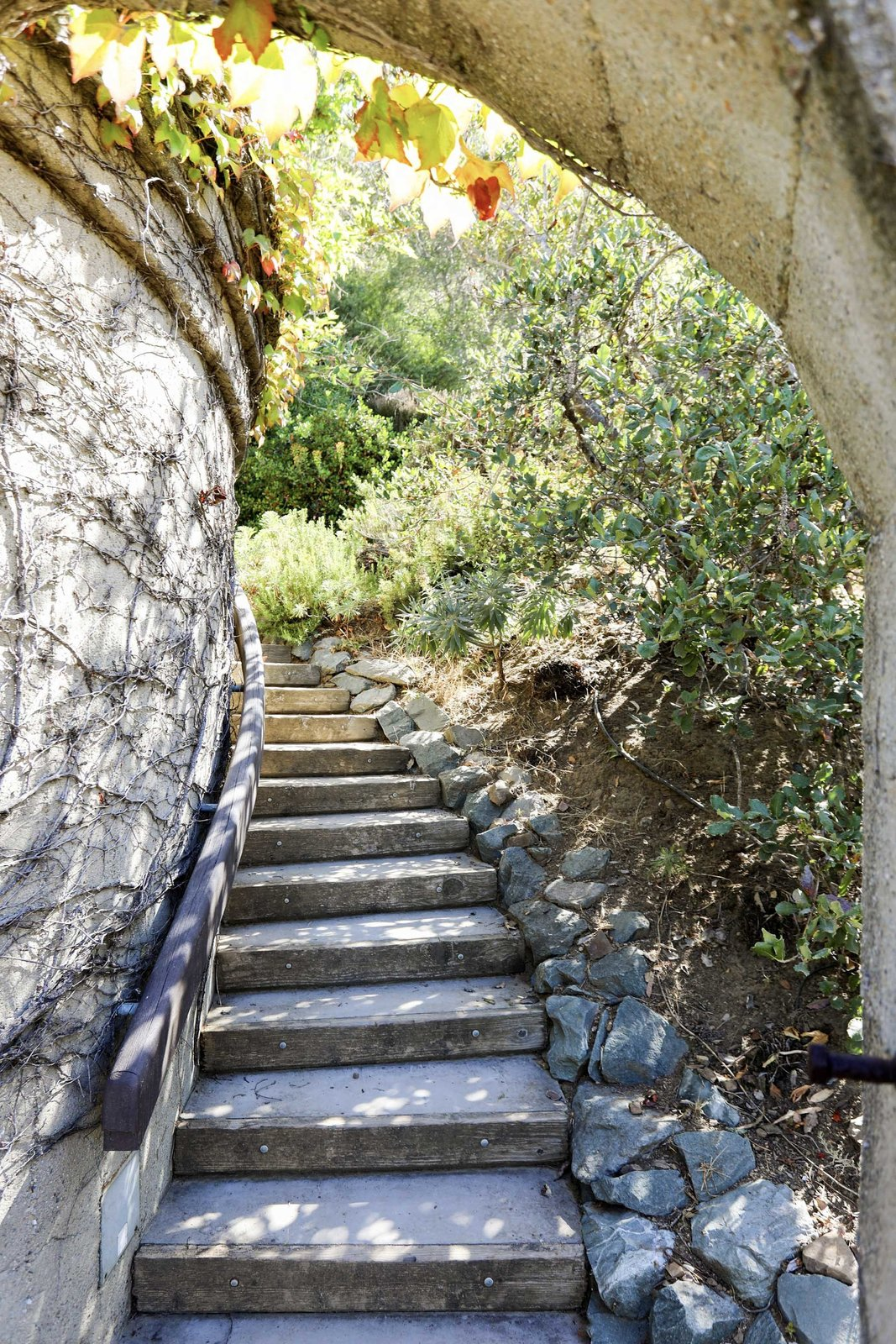 Concrete stairs wind down from the terrace to the lower-level gardens and driveway.  Photo 16 of 19 in An Alluring Berkeley Hills Home by a Case Study Architect Asks $2.9M