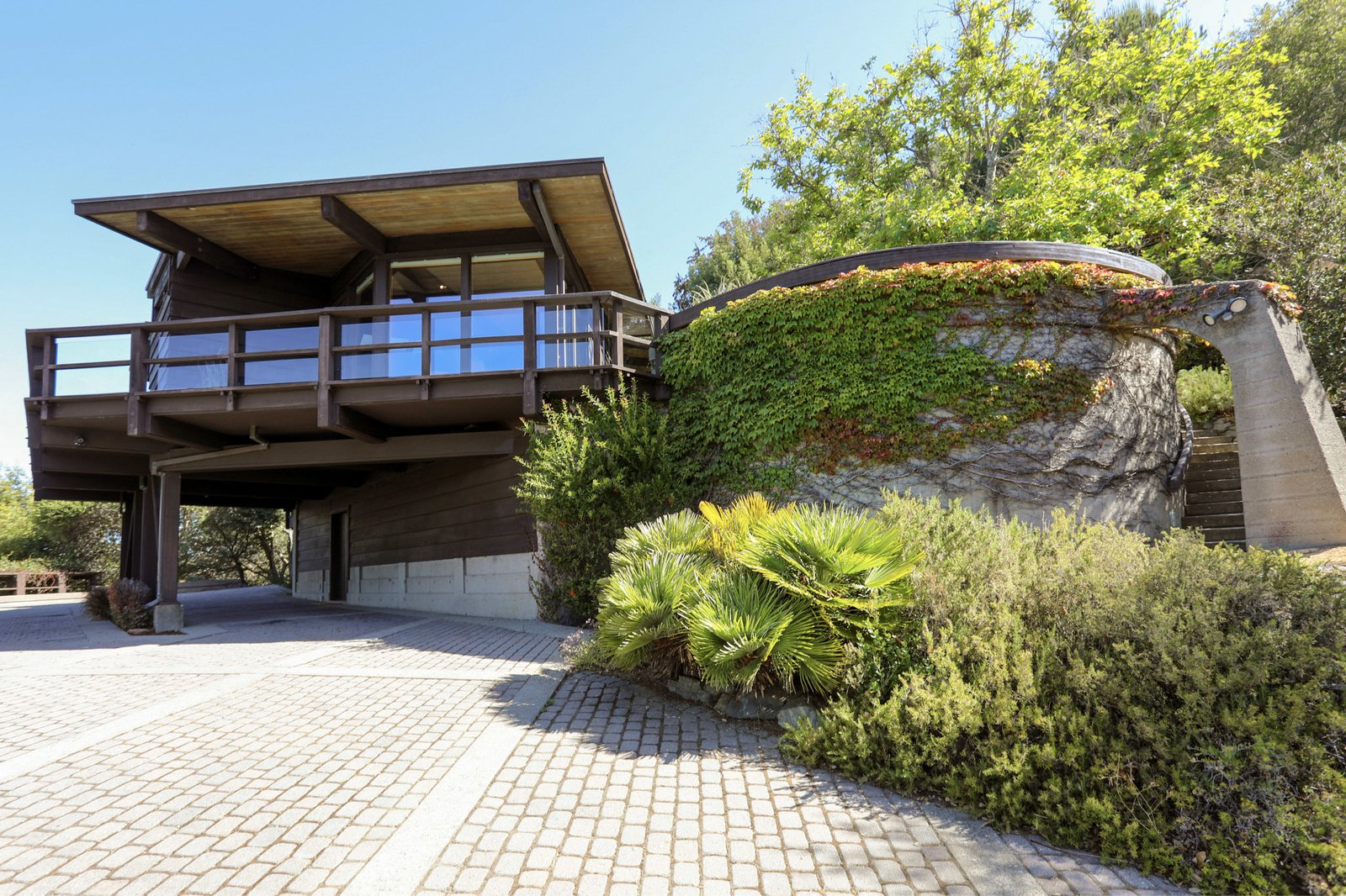 A view of the front facade shows the carport under the deck. The home's two-car garage is located further up the driveway, on the opposite side of the carport.  Photo 17 of 19 in An Alluring Berkeley Hills Home by a Case Study Architect Asks $2.9M