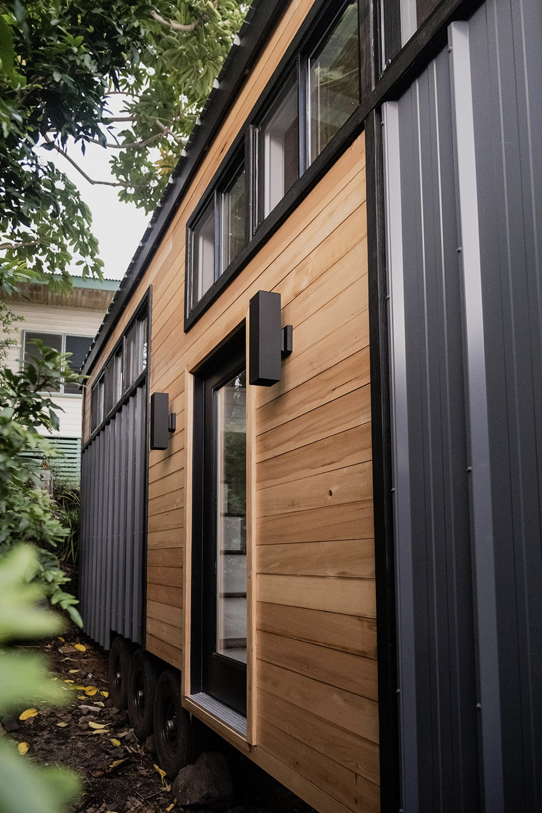 Exterior and Tiny Home Building Type Two bands of clerestory windows run along the front facade, where a single glass door is flanked by simple light fixtures to complement the metal cladding.  Photo 14 of 14 in A Hawaii-Based Couple Build a Luminous Tiny House in Just 25 Days