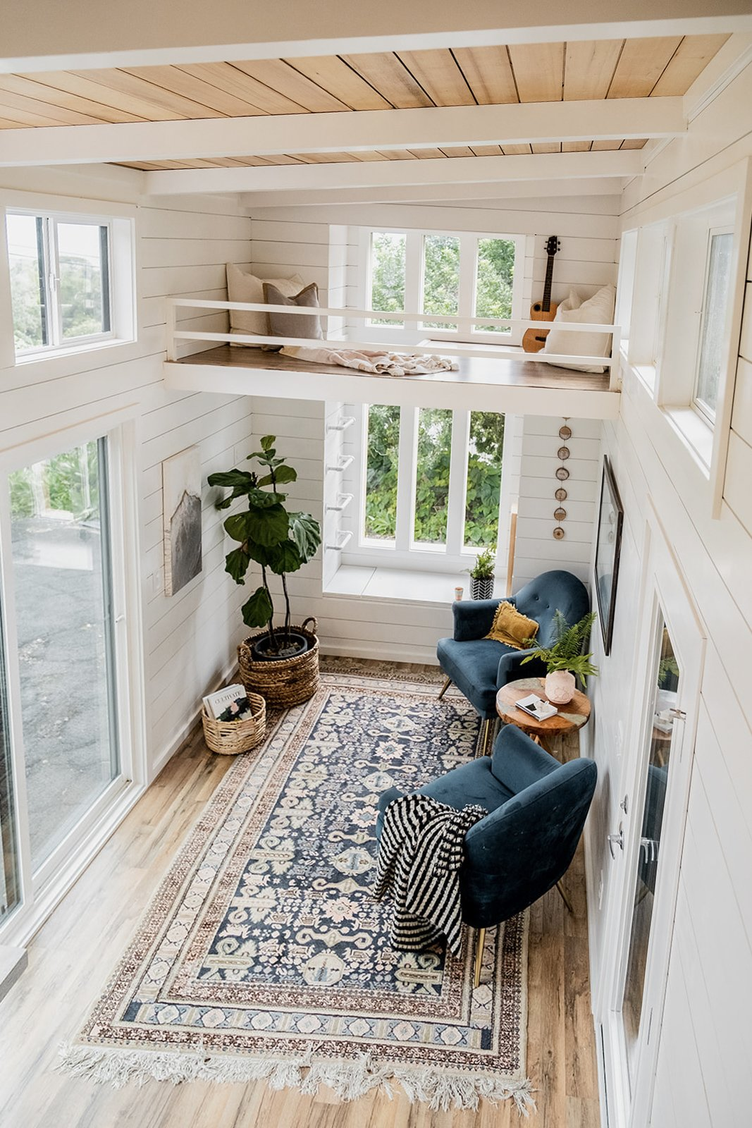 Living Room, Rug Floor, Chair, End Tables, and Medium Hardwood Floor A view from the bedroom loft.  Photo 12 of 14 in A Hawaii-Based Couple Build a Luminous Tiny House in Just 25 Days