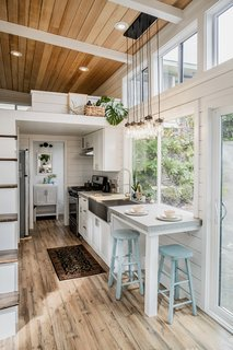 Corresponding with the exterior facade, cedar runs along the ceiling and interior walls. The back half of the home features a galley-style kitchen with full-size sink, stove, and fridge.