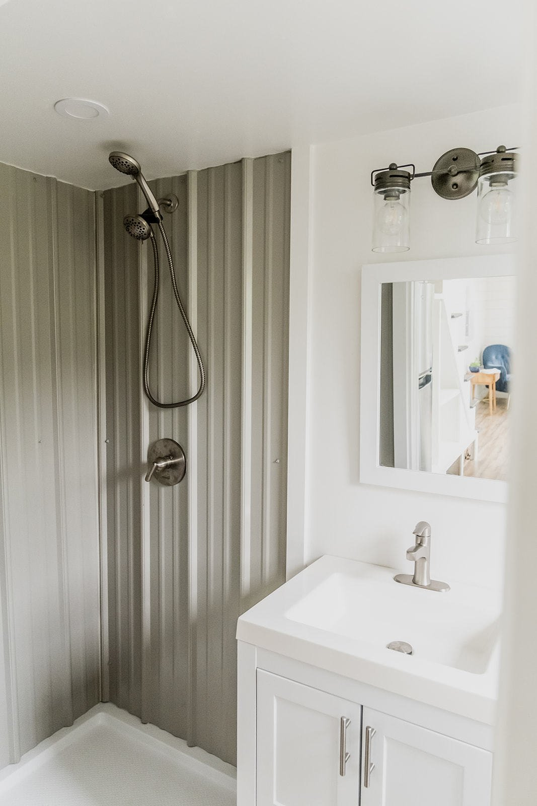 Bath Room, Granite Counter, Vessel Sink, Open Shower, Wall Mount Sink, Ceiling Lighting, and Recessed Lighting At the rear of the home, the bathroom offers a 42-inch-wide shower, as well as a central vanity and toilet.  Photo 10 of 14 in A Hawaii-Based Couple Build a Luminous Tiny House in Just 25 Days