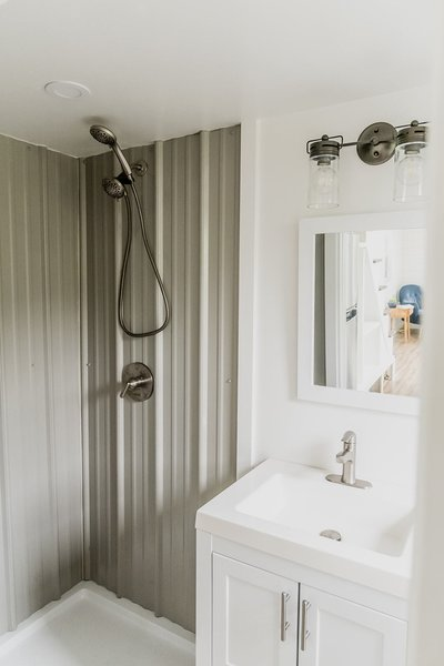At the rear of the home, the bathroom offers a 42-inch-wide shower, as well as a central vanity and toilet.