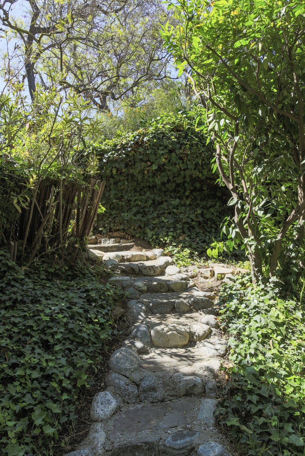 A stone pathway leads to the second home at the back of the .57-acre compound.  Photo 15 of 22 in A Lush Los Angeles Compound With a Shingle-Clad Cottage and Lime-Green Home Seeks $2M
