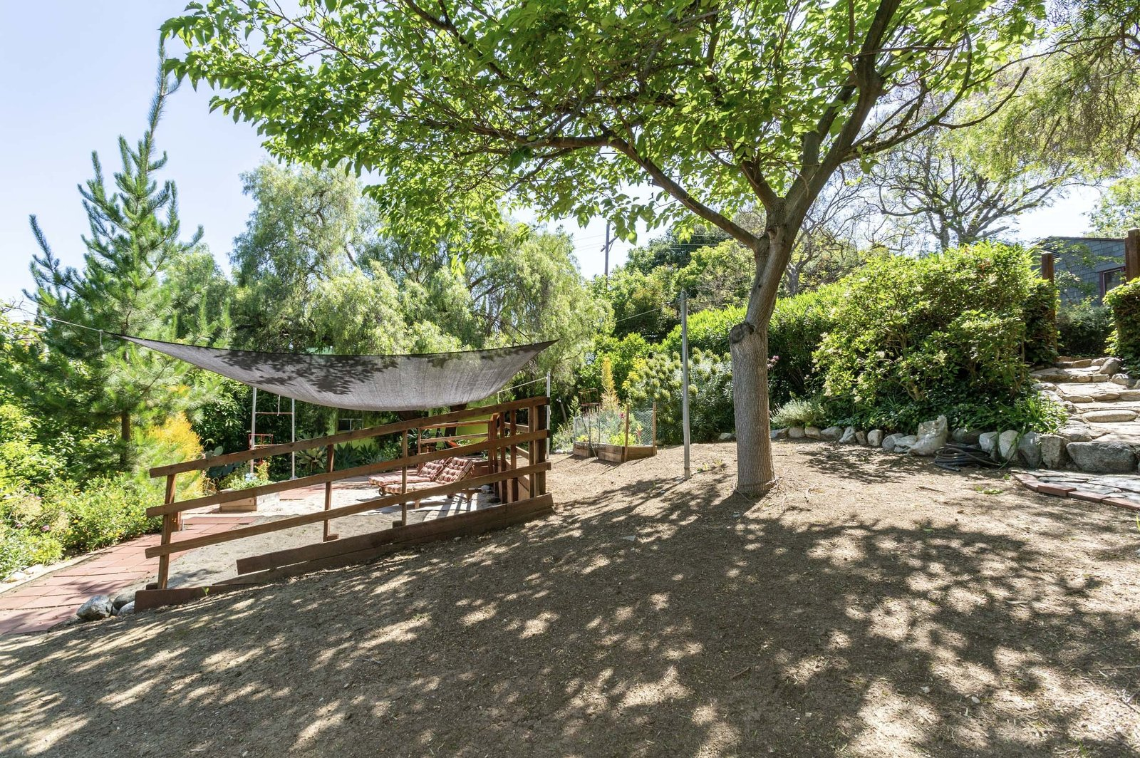 At canopy-covered patio is located in another corner, adjacent to raised vegetable beds.  Photo 14 of 22 in A Lush Los Angeles Compound With a Shingle-Clad Cottage and Lime-Green Home Seeks $2M