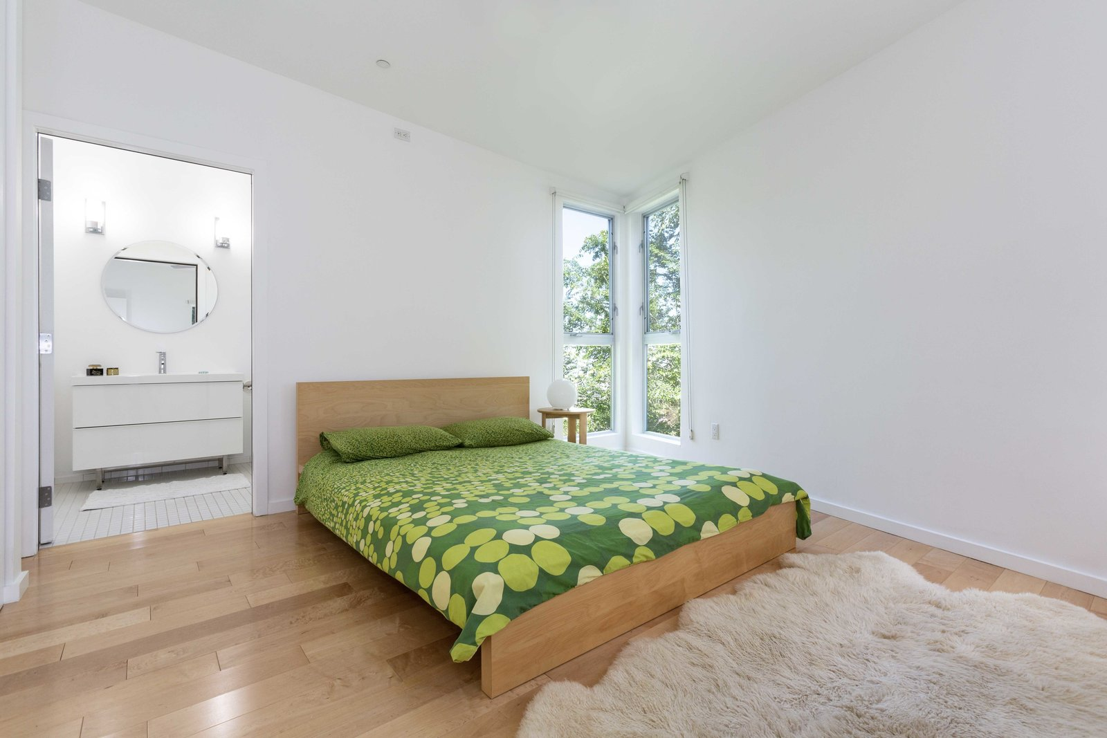 Upstairs, a principal suite features several floor-to-ceiling windows at the corner.  Photo 21 of 22 in A Lush Los Angeles Compound With a Shingle-Clad Cottage and Lime-Green Home Seeks $2M