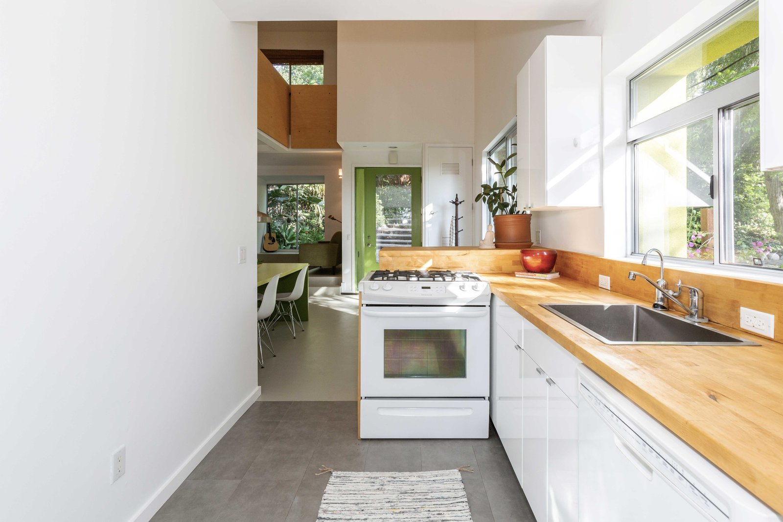 A look at the sun-lit kitchen with butcher-block countertops.  Photo 19 of 22 in A Lush Los Angeles Compound With a Shingle-Clad Cottage and Lime-Green Home Seeks $2M