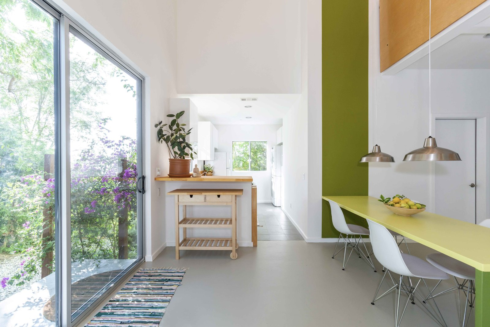 The dining area also features a built-in table. Along the opposite wall, a sliding glass door provides access to the garden.  Photo 18 of 22 in A Lush Los Angeles Compound With a Shingle-Clad Cottage and Lime-Green Home Seeks $2M