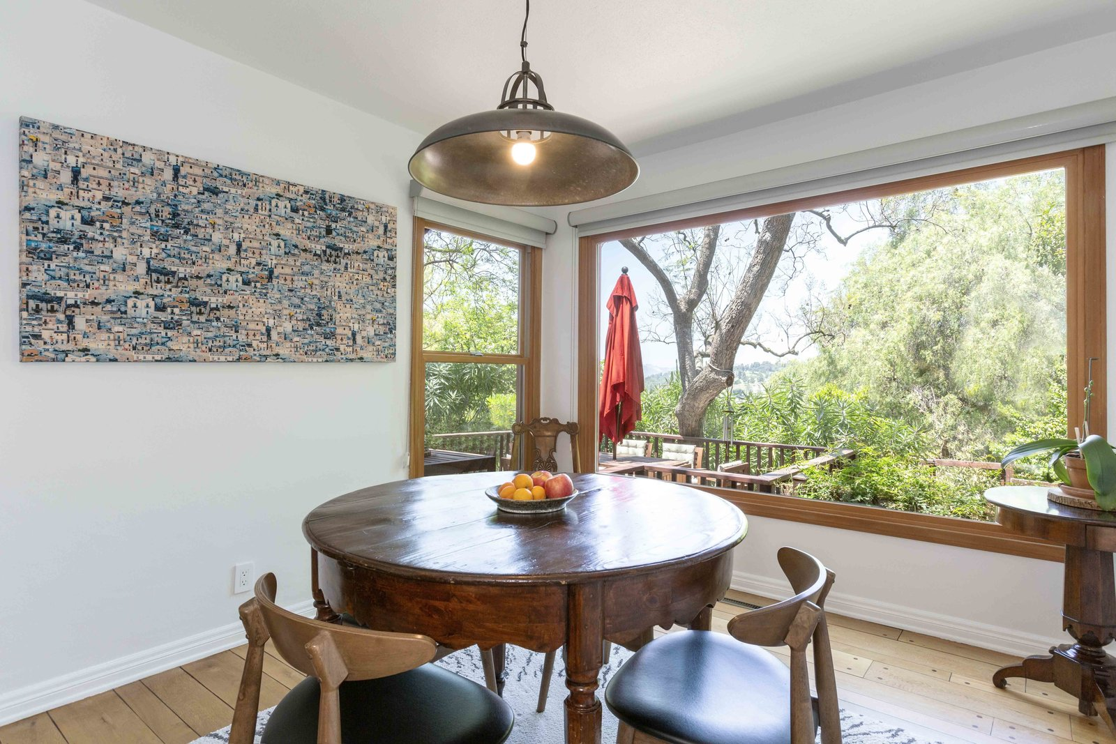 Toward the back of the cottage, another large picture window overlooks several massive oaks around the property.  Photo 7 of 22 in A Lush Los Angeles Compound With a Shingle-Clad Cottage and Lime-Green Home Seeks $2M
