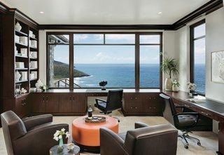 The office features a nearly full-width picture window in front of built-in desks. Views extend beyond the immediate cove to the Atlantic Ocean and horizon.