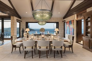 Just off the kitchen and behind the living room is a dining area. Folding glass doors achieve Feng Shui by opening the entire space up to cross-breezes and water elements on both sides.