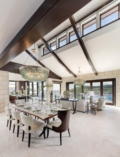 Inside, a double-height living area is topped by a row of clerestory windows and a trio of mahogany beams that swoop upward like buttresses toward a balcony. Rows of windows and multi-paneled folding doors frame postcard-worthy views of the surrounding landscape.