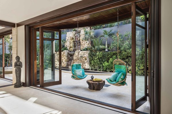 Behind the dining room table, another set of multi-paneled folding glass doors open to the backyard Zen garden—complete with a reflecting pool and waterfall.