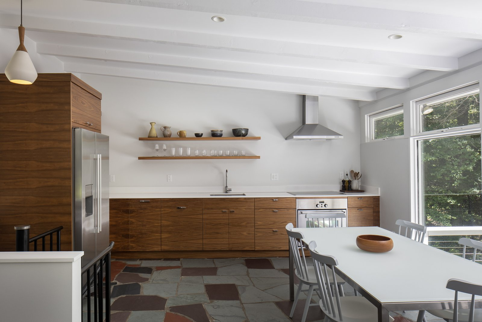 The renovated kitchen features all-new cabinetry and appliances. Open shelving takes the place of upper cabinetry, adding to the airy feeling.  Photo 5 of 15 in For $1.35M, Snag This Renovated Midcentury Retreat Nestled in a Hardwood Forest