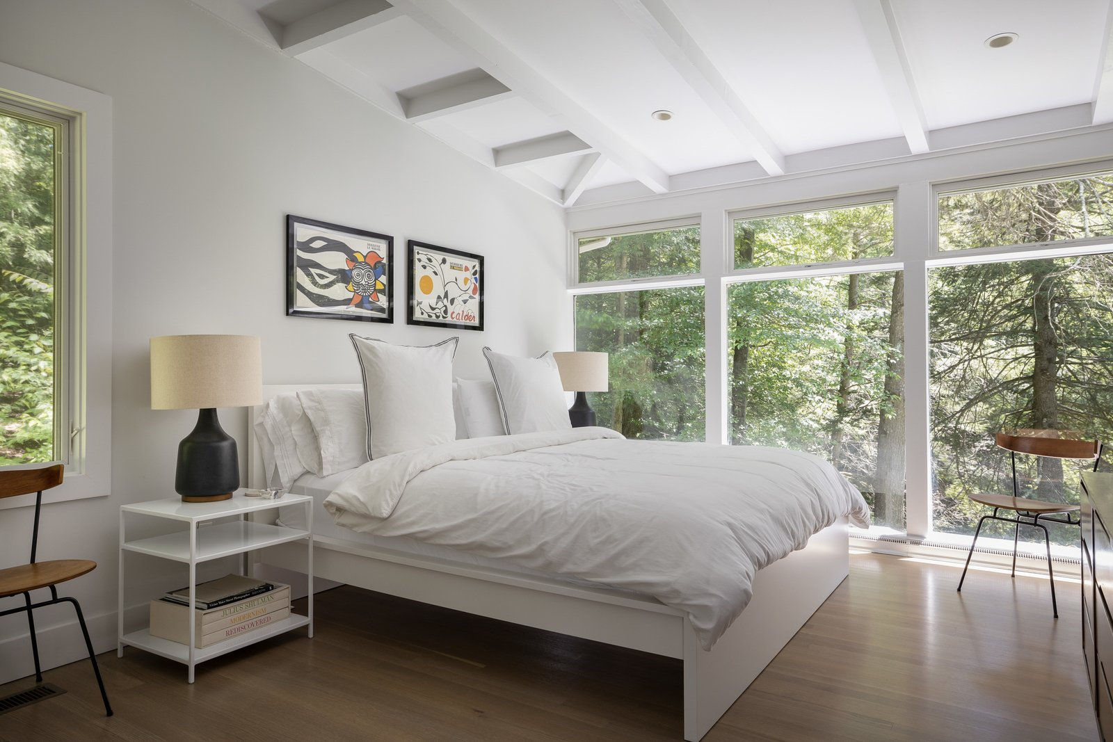 The home's three bedrooms are located down a hallway beside of the kitchen. Here, the largest bedroom features floor-to-ceiling windows overlooking the treetops.  Photo 6 of 15 in For $1.35M, Snag This Renovated Midcentury Retreat Nestled in a Hardwood Forest
