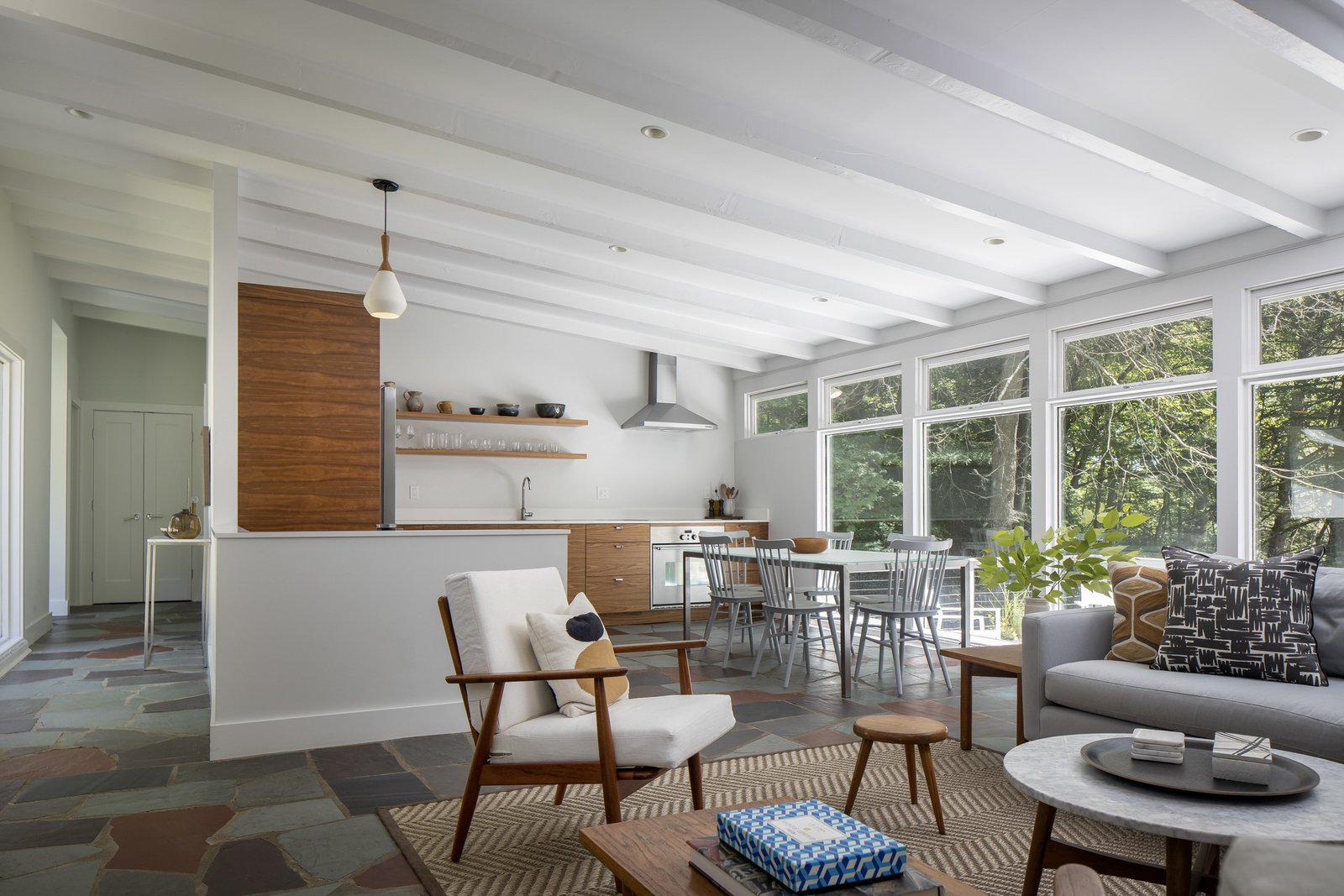 The living room flows directly into the dining area and kitchen. Exposed rafters subtly reinforce the slated roofline and draw the eye toward the wall-to-wall windows.  Photo 4 of 15 in For $1.35M, Snag This Renovated Midcentury Retreat Nestled in a Hardwood Forest