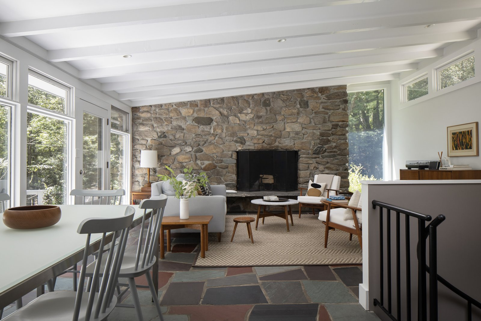 Inside, understated finishes allow the stone fireplace and floor-to-ceiling windows to stand out. Slate tiles line the floors while clerestory windows provide sunlight from the opposite direction.  Photo 2 of 15 in For $1.35M, Snag This Renovated Midcentury Retreat Nestled in a Hardwood Forest