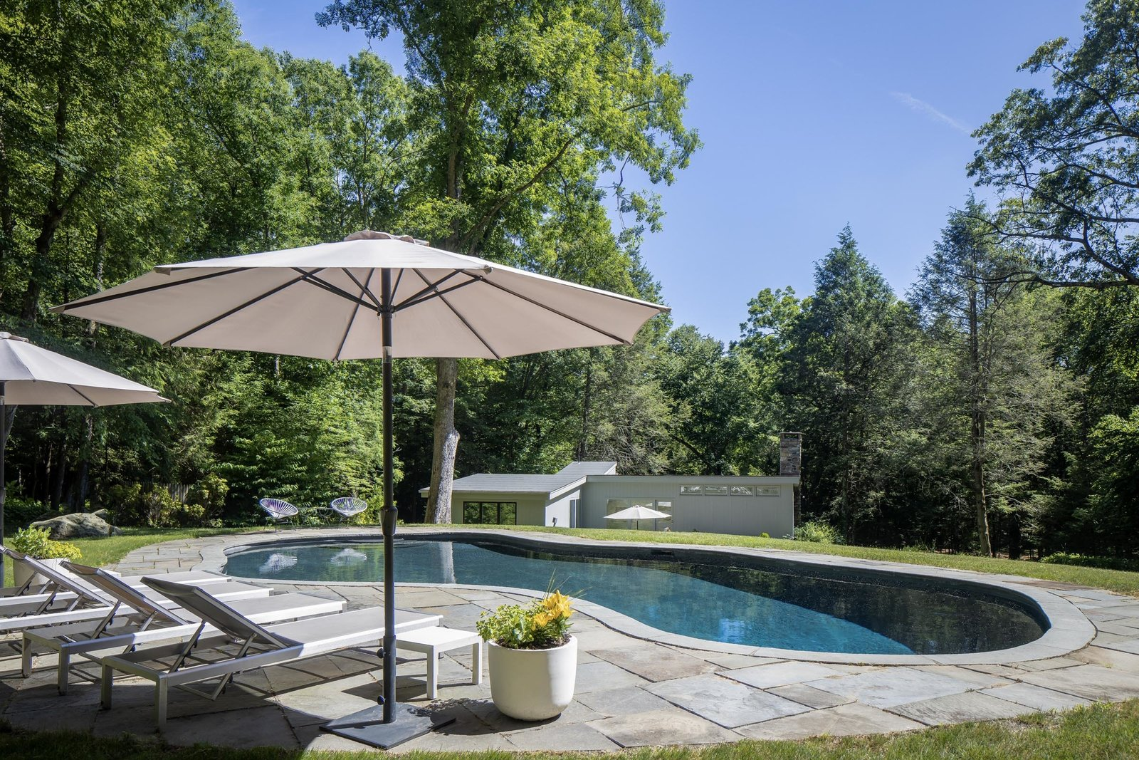 The gunite swimming pool takes a picturesque position along a hilltop beside the house. A surrounding stone patio provides an additional space to soak up some sunshine.  Photo 14 of 15 in For $1.35M, Snag This Renovated Midcentury Retreat Nestled in a Hardwood Forest