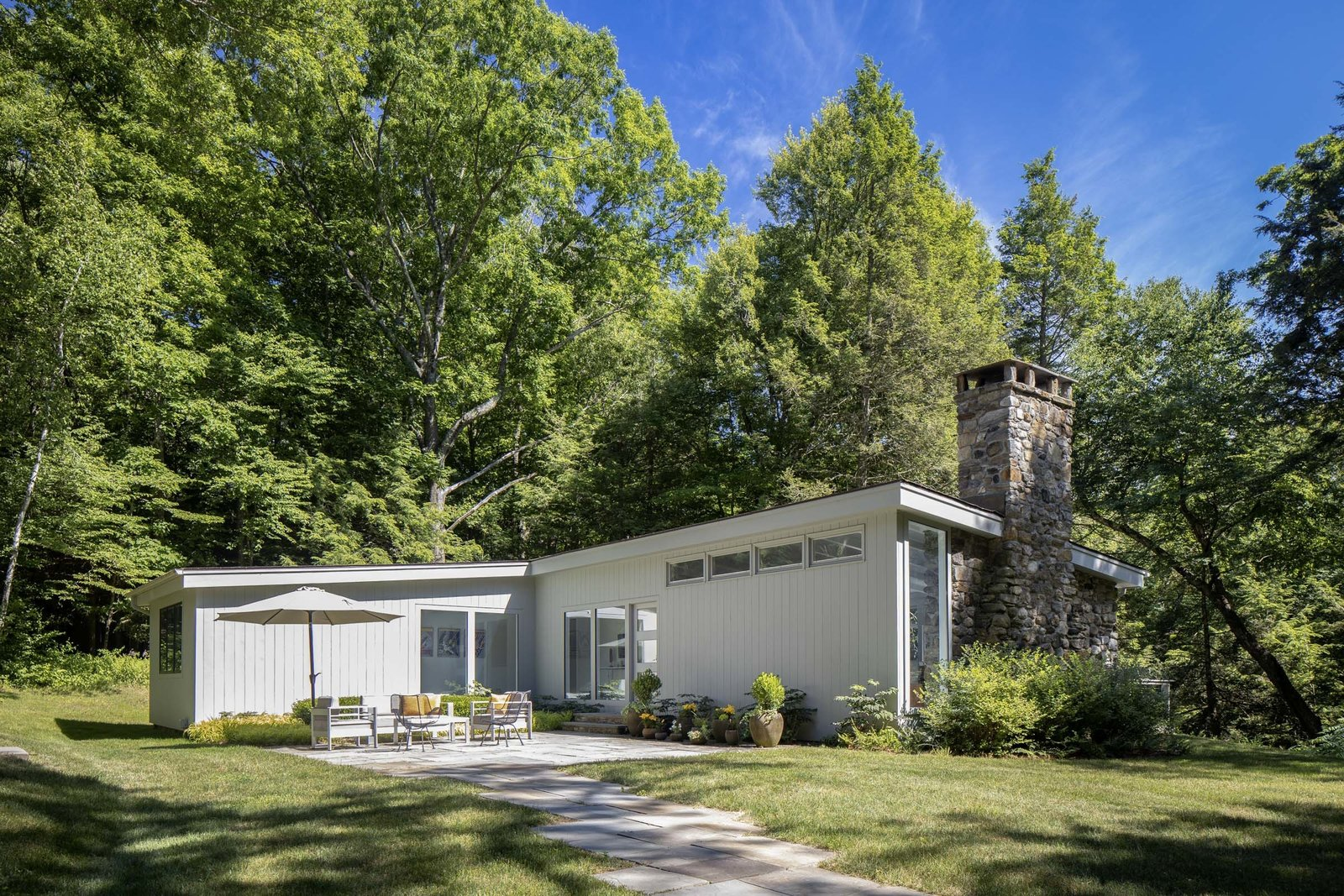 Located in Washington, Connecticut, about two hours north of New York City, this 1957 home is back on the market after a multi-year renovation. A stone fireplace and wall cap one end of the structure and provides a focal point for interior spaces.  Photo 1 of 15 in For $1.35M, Snag This Renovated Midcentury Retreat Nestled in a Hardwood Forest