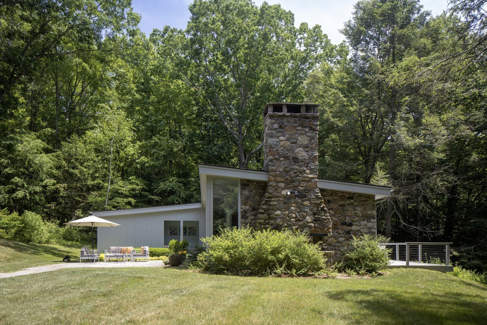 Outside, the home offers a sunny patio on one side and a large deck on the other. A large lawn surrounds the home, which is sited in a clearing off the road and in the middle of the acreage.  Photo 12 of 15 in For $1.35M, Snag This Renovated Midcentury Retreat Nestled in a Hardwood Forest