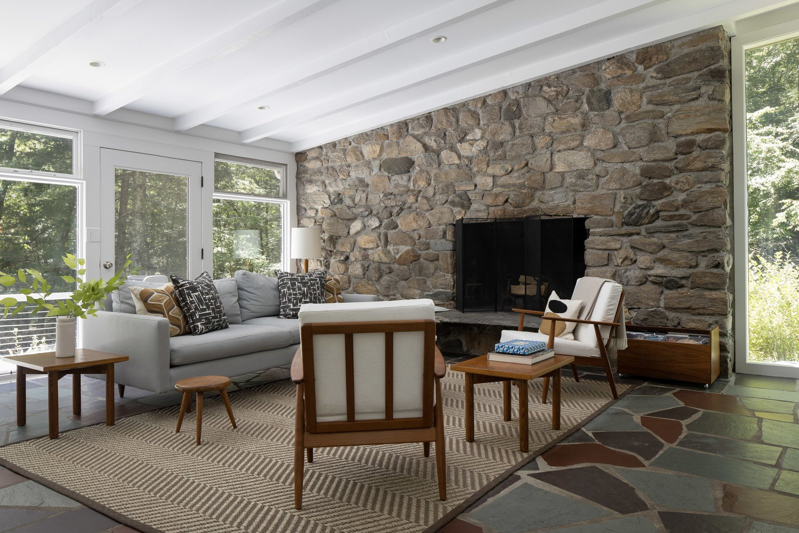 Crisp, white finishes balance the commanding stone fireplace, which is original to the home. A door leads to the back deck.  Photo 3 of 15 in For $1.35M, Snag This Renovated Midcentury Retreat Nestled in a Hardwood Forest