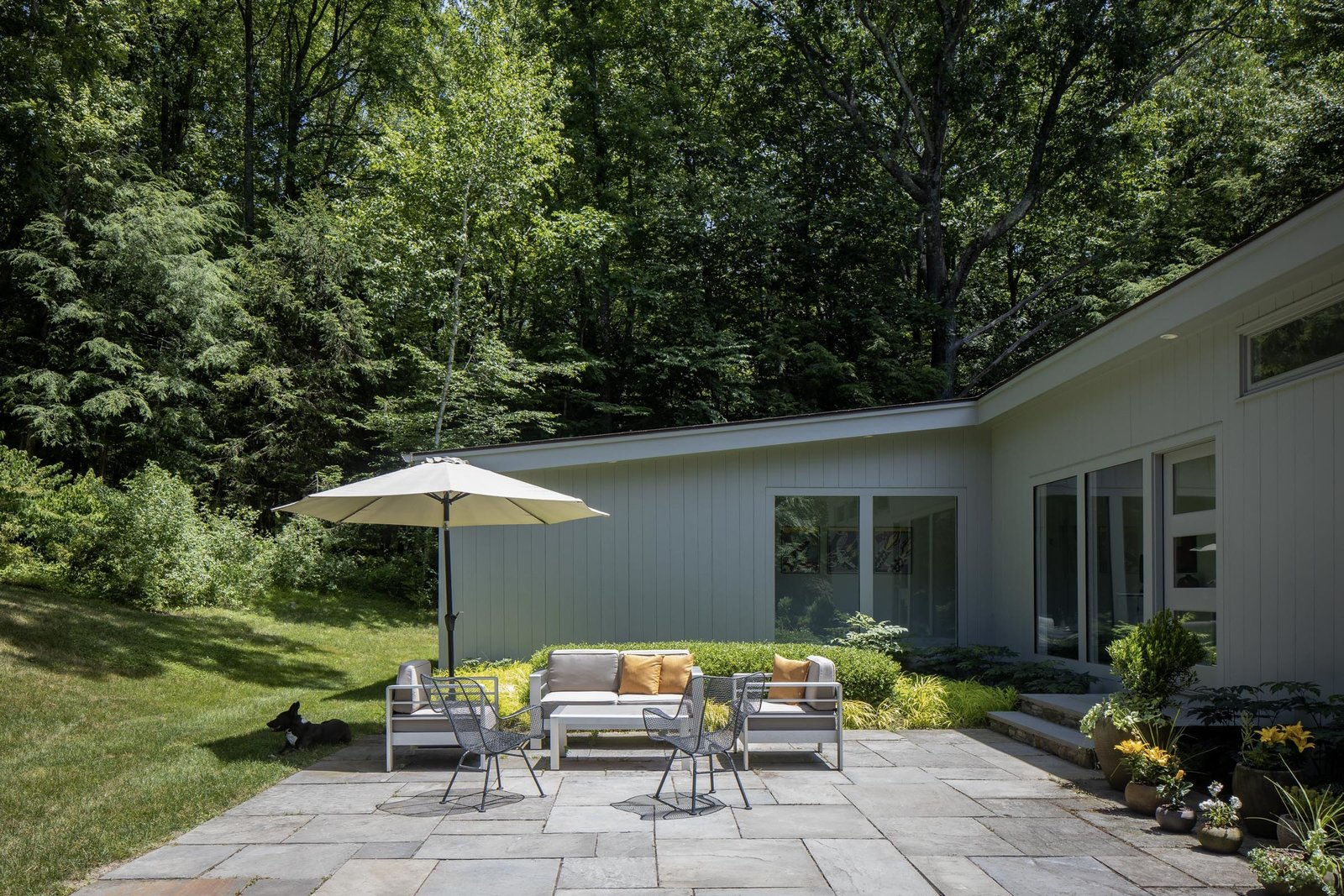 A closer look at the stone patio. A door to the right also serves as the home's main entrance, leading into the open living and dining area.  Photo 13 of 15 in For $1.35M, Snag This Renovated Midcentury Retreat Nestled in a Hardwood Forest