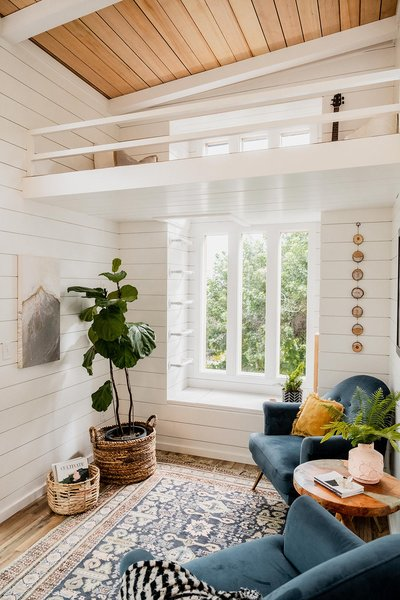At one end of the home, the living area features a set of custom vertical windows with a small loft area above. A window seat with built-in storage occupies space over the trailer tongue.