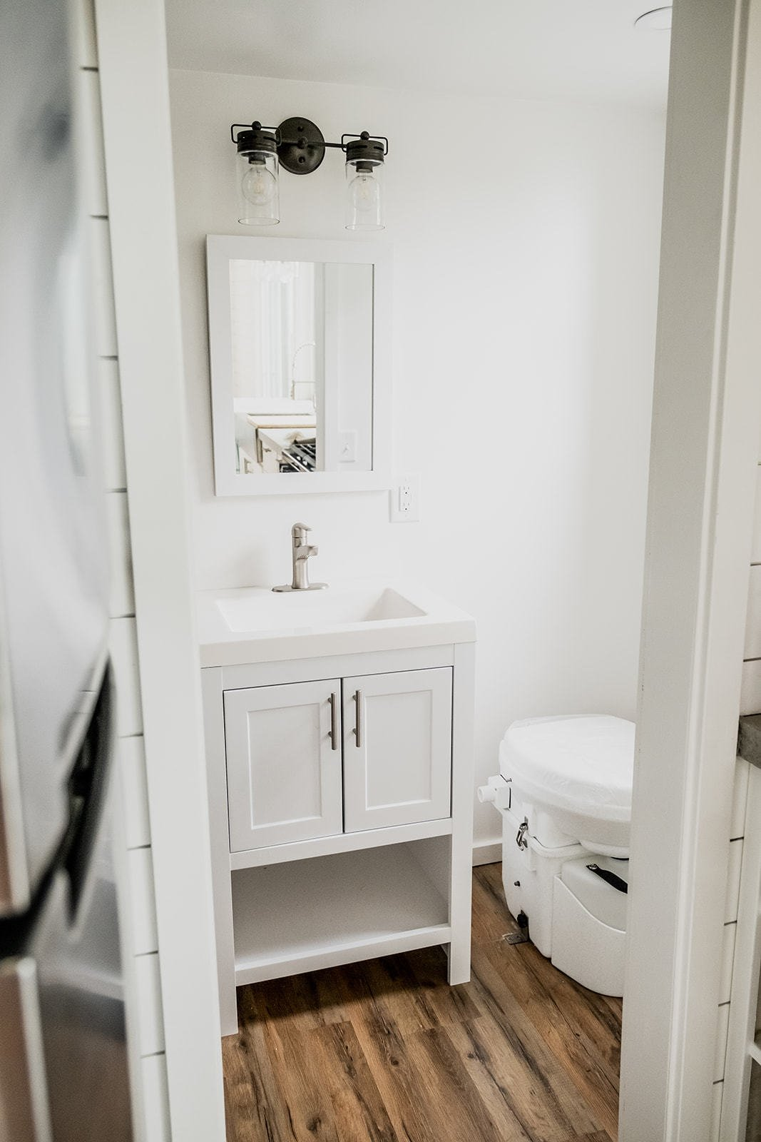 Bath, Granite, Wall Mount, Vessel, One Piece, Medium Hardwood, Wall, and Accent Both traditional and composting toilets are available to accommodate off-grid living.  Bath Vessel Accent Photos from A Hawaii-Based Couple Build a Luminous Tiny House in Just 25 Days