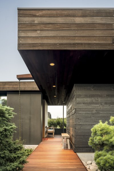 A walkway leads from a street-facing gate through a Zen garden and central courtyard to the home's front door. To the right, a small garden shed is clad in reclaimed timbers, stacked and blackened, while the overhang is clad in naturally weathered cedar.
