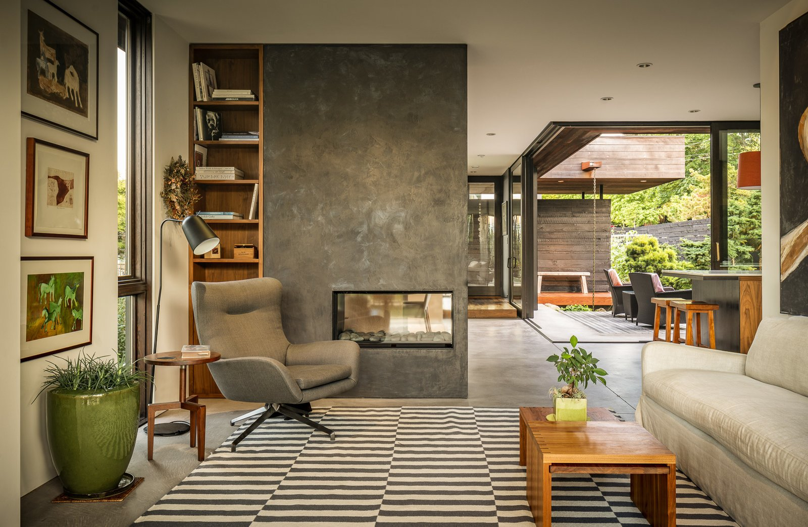 The cozy family room occupies a corner opposite from the courtyard. A full-height window and built-in bookcase flank a multisided fireplace.